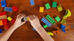 Girl playing in the colored blocks at the table Stock Footage
