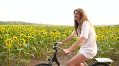 Young lady rides a bike at sunflower field Stock Footage