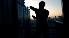 Silhouette of man applying anti-perspirant on armpit on terrace, slow motion Stock Footage