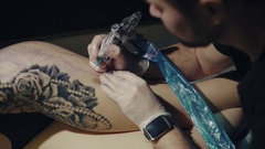 Close-up of hands of tattoo artist in gloves tattooing a pattern on body Stock Footage