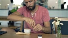 Young man adding sugar into coffee and mixing sitting in cafe, 4k Stock Footage