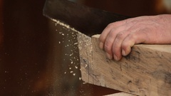 Close up of carpenter sawing a wooden post with hand-saw. Stock Footage