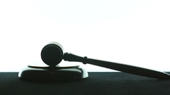 Judge hitting gavel 3 times against white background Stock Footage