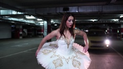 Ballerina dancing in the underground parking in the headlights of the car 4K Stock Footage
