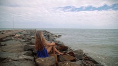 Gorgeous young girl with a beautiful figure posing and walks along the seashore Stock Footage