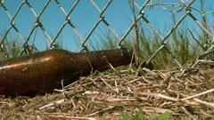 Beer Bottle Polution Near Fence, 4K Stock Footage
