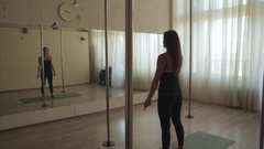 Young girl doing a workout in the gym with large mirrors, a dance hall Stock Footage