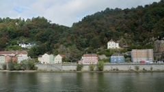 Traffic rolls by a row of houses on this bank of the Danube River time lapse Stock Footage