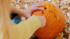 Pumpkin lying on yellow autumn leaves. Woman cuts in her face monster-lantern Stock Footage