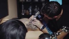 Tattoo artist make tattoo at the studio Stock Footage