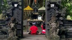 Young couple making offerings and praying at Gunung Kawi Temple. Bali, Indonesia Stock Footage