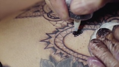 Close-up of hands of tattoo artist in gloves tattooing a pattern on body macro Arkistovideo