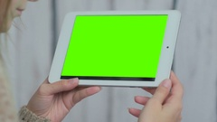 Woman looking at tablet computer with green screen Stock Footage