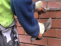 Man repointing red brick wall Stock Footage