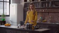 Woman preparing dinner in apartment Stock Footage