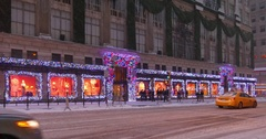 Snowy Establishing Shot of Saks Fifth Avenue Decorated for Christmas  	 Stock Footage