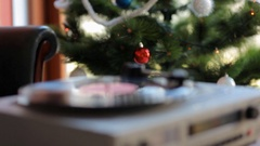In vintage gramophone playing a vinyl record on a background of Christmas tree. Arkistovideo