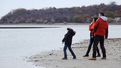 Parents with their young son throw stones into the lake Stock Footage