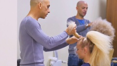 Two Barbers or stylist makes styling of curly hair of model by hairdresser in Stock Footage