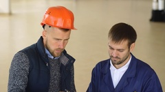 A team of construction workers with orange helmets at work place in a factory Stock Footage
