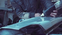 Worker panel beating in auto repair garage Stock Footage