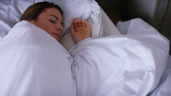 4K Young sleeping woman changes her position in bed as she rolls over Stock Footage