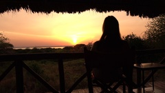 CLOSE UP: Girl sitting on wooden chair on veranda watching golden light sunrise Stock Footage