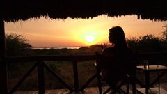 CLOSE UP: Girl relaxing on veranda watching stunning nature and golden sunrise Stock Footage