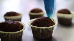Decorating chocolate cupcake with cream. Confectioner making cupcakes for party Stock Footage