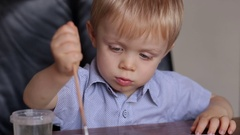 A cute little boy is drawing. Portrait of a small child. Stock Footage