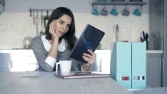 Businesswoman reading news on tablet computer and drinking coffee by table in of Stock Footage