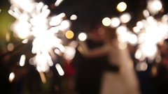 Sparkler in hands on a wedding - bride, groom and guests holding lights in Stock Footage
