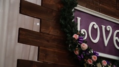 Love inscription on a wooden background, flashing lights and flowers. Decorative Stock Footage