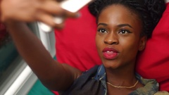 Portrait of beautiful african-american girl making funny selfies lying in bed Stock Footage