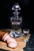 Bottle and shot glasses with vodka with slices of smoked meat on brown pack.. Stock Photos