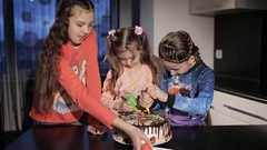 Three funny little girls draw a Christmas tree and Santa on the cake. Cake Stock Footage