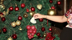 Pregnant woman decorating christmas tree with baby booties. Stock Footage