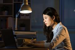 Asian business woman use laptop working overtime late night Stock Photos