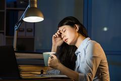 Asian business woman drink coffee refreshing working overtime late Stock Photos