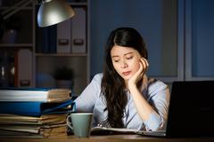 Asian business woman working overtime late night in office Stock Photos