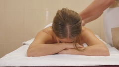 Smiling young woman laying on massage table and showing thumbs up Stock Footage