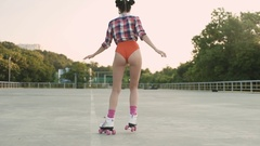 Back view of a girl in red swimsuit on roller skates  Stock Footage