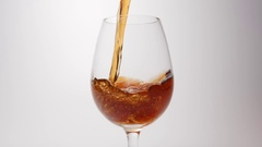 SLOW MOTION: Brown beverage pour into a glass on a white background Stock Footage