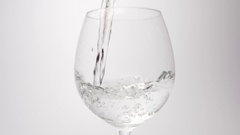 SLOW MOTION: Water pour into a wine glass on a white background Stock Footage