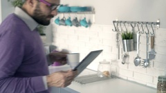Young man reading news on tablet and drinking coffee in kitchen  Stock Footage
