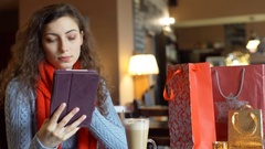 Pretty girl browsing internet on tablet in the festive cafe, steadycam shot Stock Footage