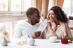 Pleased African American woman getting a ticket from her boyfriend Stock Photos