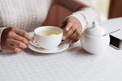 White teacup in the hands of African American man Stock Photos