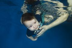 Little boy in blue shirt posing under the water in the pool Kuvituskuvat