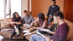 Group of multi ethnic young students preparing for exams in home interior Stock Footage